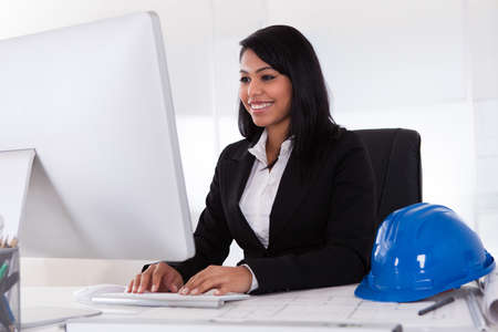 Happy Young Female Architect Using Computer In Office Stock Photo - 19979855