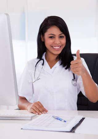 Happy Female Doctor Using Computer And Gesturing Thumbs-Up Sign photo