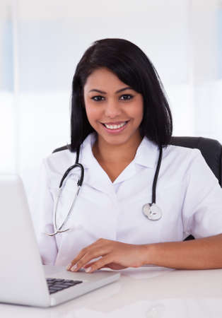 Pretty Young Confident Doctor Using Laptop In Clinic photo