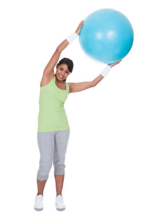 Young Woman Exercising With Pilates Ball Over White Background photo