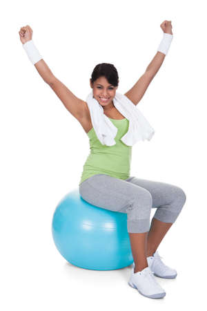 Young Woman Sitting On Pilates Ball With Arm Raised Over White Background