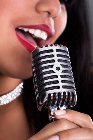 Close-up Of Young Beautiful Woman Singing In Microphone photo