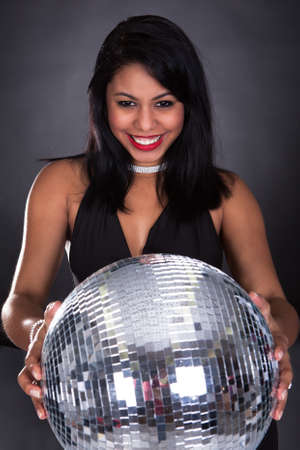 Young Woman Holding Disco Ball Over Black Background photo