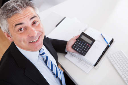 the bookkeeper: Portrait Of Mature Businessman Calculating Finance At Office