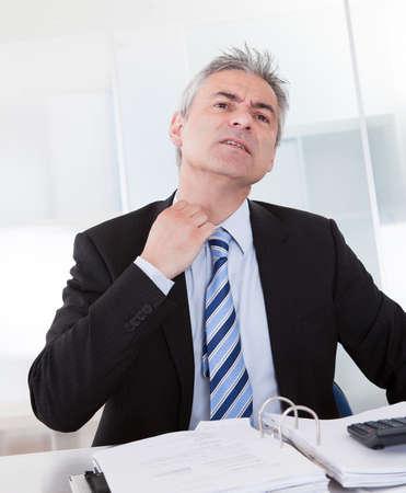 perspiring: Portrait Of Mature Businessman Adjusting Collar At Desk