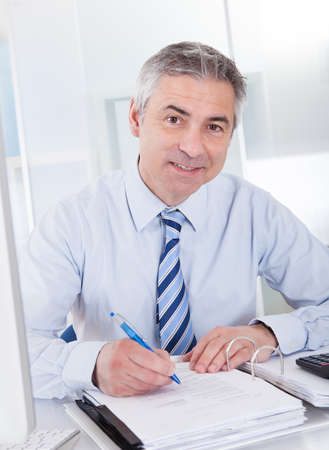 Portrait Of Mature Businessman Calculating Finance At Office photo