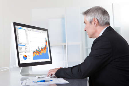 Mature Businessman Looking At Computer Anzeigen Diagramm Lizenzfreie Bilder