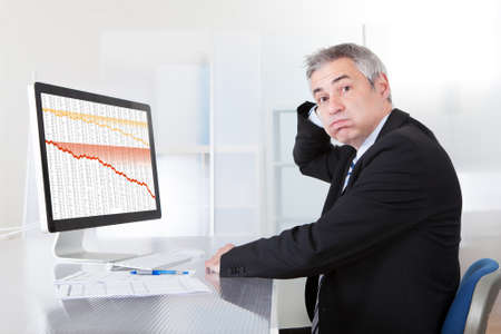 worried businessman: Portrait Of Confused Businessman With Computer In Office Stock Photo