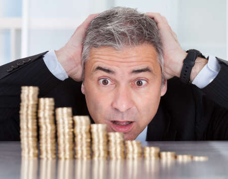 recession: Shocked Mature Businessman Looking At Descending Stack Of Coins