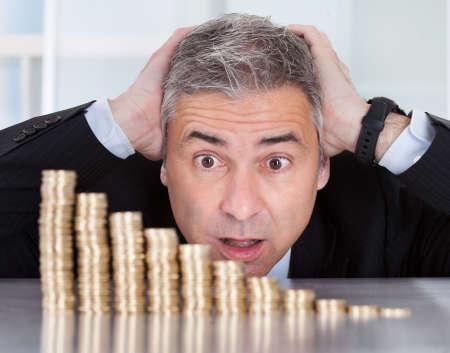 Zszokowany Starsza biznesmen, patrzÄ…c na stos monet malejÄ…cy Zdjęcie Seryjne