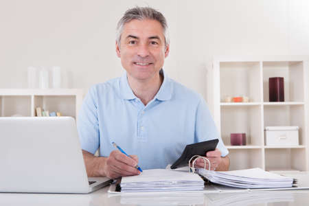 Portrait Of Happy Mature Man Calculating Finances photo