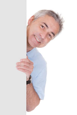 Mature Man Standing Behind Placard Over White Background photo