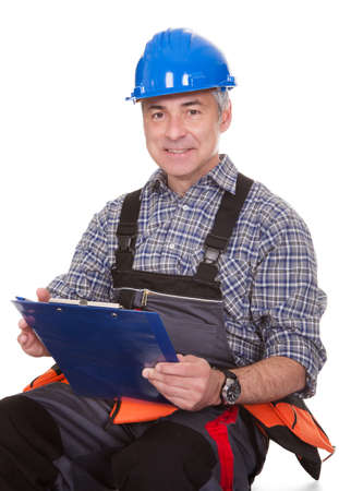 Mature Technician Holding Clipboard Over White Background