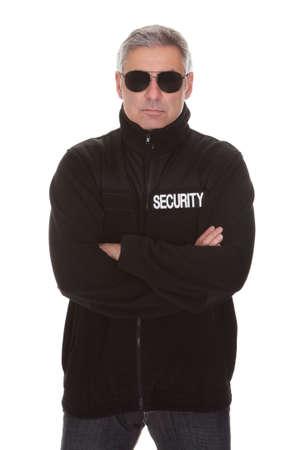 agent de sécurité: Homme mûr de sécurité permanent sur fond blanc