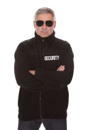 law enforcer: Mature security man standing over white background