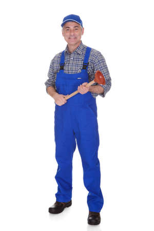 Portrait Of Male Plumber Holding Plunger Over White Background photo