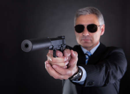 violence and trigger: Close-up Of Male With Handgun Over Black Background Stock Photo