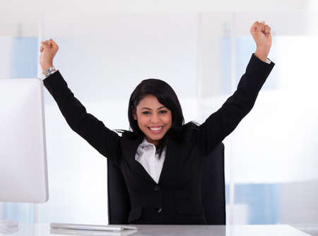 Portrait Of Happy Businesswoman With Hand Raised photo