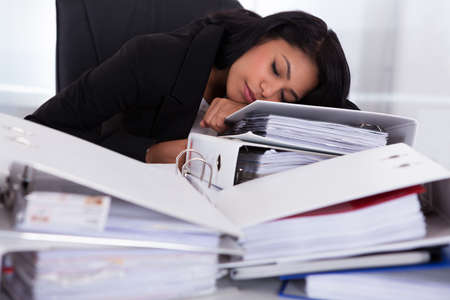 workaholic: Young Businesswoman Sleeping On Piles Of Folders In Office Stock Photo
