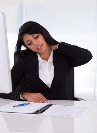 cramp: Young Businesswoman Sitting On Chair And Holding Her Neck In Pain Stock Photo