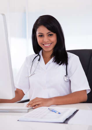 Pretty Young Confident Doctor Using Computer In Clinic photo