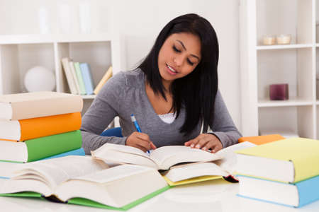 high school students: Portrait Of Young Happy Woman Studying At Home Stock Photo