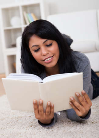Happy Young Woman Lying On Carpet And Reading Book photo