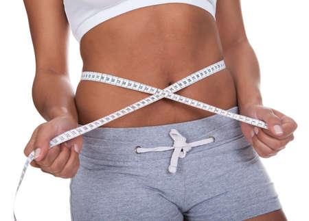 Portrait Of Young Woman Measuring Her Waistline Over White Background photo