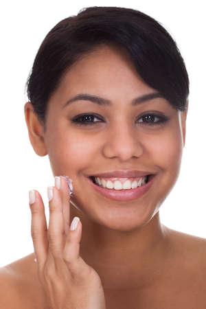 Young Woman Applying Cream On Her Face Over White Background photo