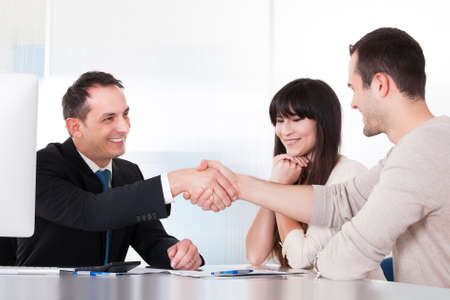 insurance consultant: Consultant Shaking Hands With A Man In Office Stock Photo