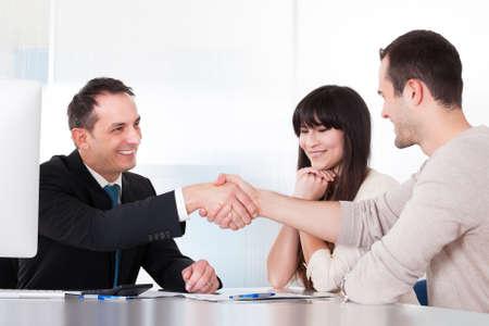 Consultor estrechándole la mano con un hombre en la oficina