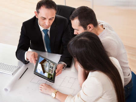 business consultant: Happy Young Couple Discussing With Consultant In Office