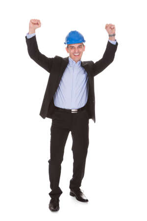 Excited Male Architect With Arms Raised Over White Background Stock Photo - 20201635