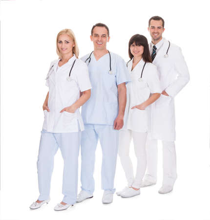 Happy Group Of Doctors Standing Over White Background photo