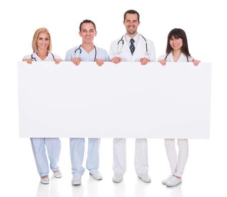 白い背景の上のプラカードを持って幸せな医師のグループ