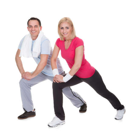 Happy Young Couple Exercising Over White Background photo