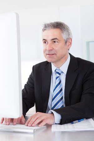 revisando documentos: Feliz hombre de negocios maduro que trabaja en el escritorio en la oficina Foto de archivo