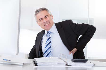dolor de espalda: Retrato del hombre de negocios mayor que sufre de dolor de espalda