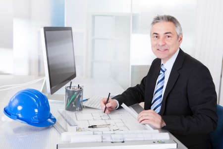 architect tools: Portrait Of Mature Architect Male With Blueprint In The Office