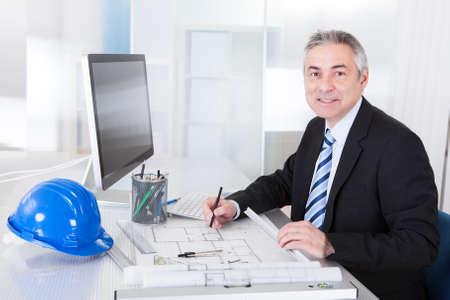 ingeniero civil: Retrato de maduro Arquitecto Hombre Con El Modelo En La Oficina Foto de archivo