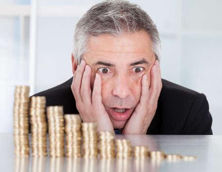 degrading: Shocked Mature Businessman Looking At Descending Stack Of Coins