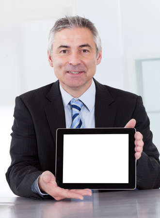 Portrait Of Happy Mature Businessman Holding Digital Tablet photo