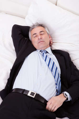 mature businessman: Portrait Of Thoughtful Mature Businessman Relaxing On Bed