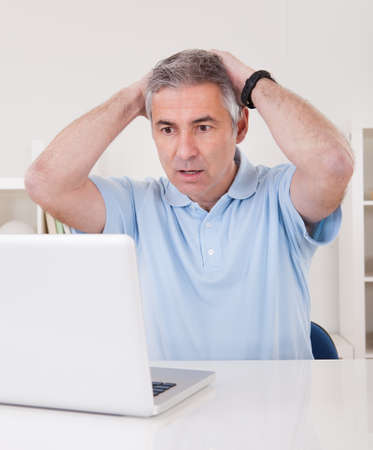 unhappy worker: Thoughtful Businessman Working On Laptop At Home