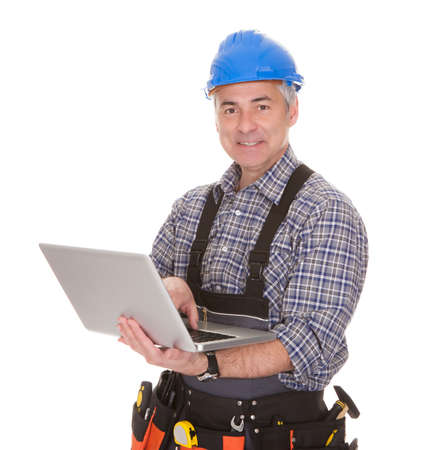 jumpsuit: Cheerful Technician Holding Laptop Over White Background Stock Photo