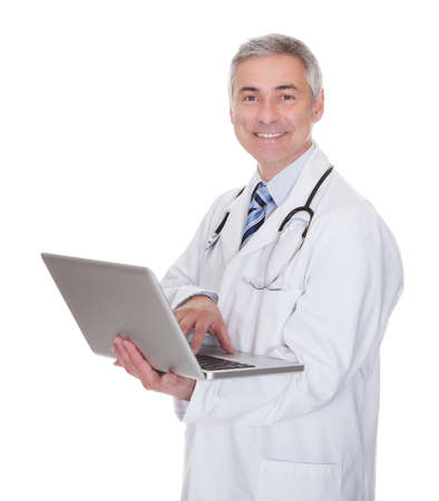 Portrait Of Male Doctor Using Laptop Over White Background photo