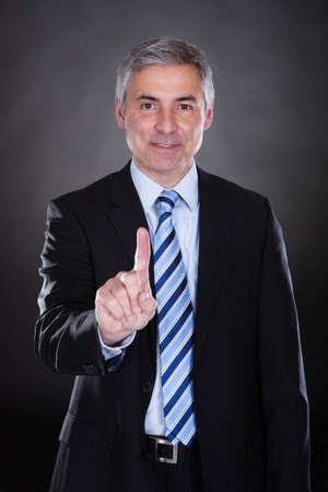Businessman touching the screen over black background photo