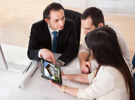 Happy Young Couple Discussing With Consultant In Office photo