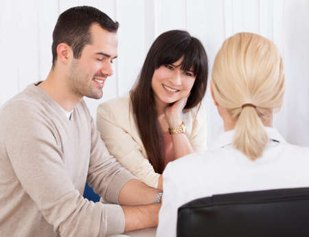 Happy Doctor Discussing With Couple In Clinic photo