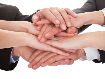 coalition: Close-up Of Businesspeople Hands Stacking Together Over White Background Stock Photo